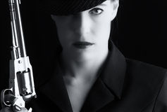 Mulher perigosa no preto com revólver de prata Foto de Stock