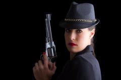Mulher perigosa no preto com revólver de prata Fotografia de Stock