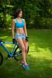 A mulher perto da bicicleta imagens de stock royalty free