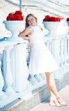 mulher perto das flores vermelhas nos vasos brancos Fotografia de Stock Royalty Free