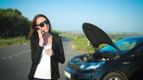 A mulher perto de um carro quebrado na estrada está chamando para o auxílio A menina preocupada nova está usando um telefone para vídeos de arquivo