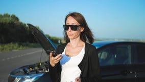 A mulher perto de um carro quebrado na estrada está chamando para o auxílio A menina preocupada nova está usando um telefone para filme