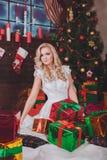 Mulher perto de uma árvore de novo-ano com presentes e velas Imagem de Stock Royalty Free