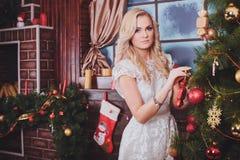 Mulher perto de uma árvore de novo-ano com presentes e velas Fotografia de Stock Royalty Free