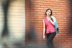 Mulher perto de uma parede de tijolo Fotos de Stock