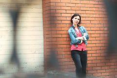 Mulher perto de uma parede de tijolo Foto de Stock