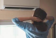 Mulher perto do condicionador de ar fotos de stock