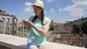 Mulher perto do móbil romano do uso do fórum O turista fêmea procura o sentido através do app em linha com mapa da cidade vídeos de arquivo
