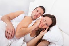 Mulher perturbada com o homem que ressona Foto de Stock
