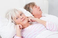 Mulher perturbada com o homem que ressona Imagens de Stock