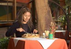 Mulher peruana nova bonita que come a pizza em um r Imagens de Stock Royalty Free