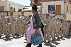 Mulher peruana tradicional que passa por um grupo de alunos Fotografia de Stock Royalty Free