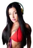 Mulher pesadamente tattooed dos jovens que escuta fones de ouvido Foto de Stock Royalty Free
