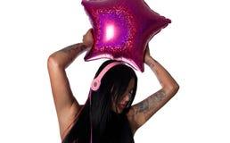 Mulher pesadamente tattooed dos jovens que escuta fones de ouvido Imagens de Stock Royalty Free