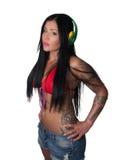 Mulher pesadamente tattooed dos jovens que escuta fones de ouvido Fotos de Stock Royalty Free