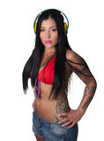 Mulher pesadamente tattooed dos jovens que escuta fones de ouvido Fotografia de Stock Royalty Free