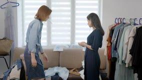 A mulher pessoal do imagem-fabricante está trabalhando com o cliente fêmea em sua casa, estão vendo a roupa e a seleção video estoque