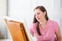 A mulher pinta a imagem na lona na armação Fotografia de Stock Royalty Free