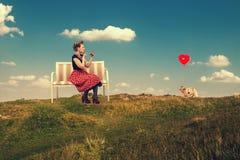 A mulher pinta os bordos com o batom que senta-se em um sofá na natureza Imagens de Stock Royalty Free
