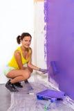 A mulher pinta a parede pelo rolo roxo Fotos de Stock Royalty Free