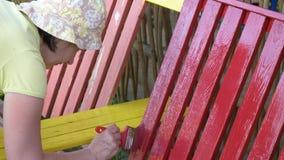 A mulher pinta um banco com pintura vermelha vídeos de arquivo