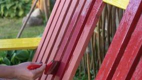 A mulher pinta um banco com pintura vermelha video estoque
