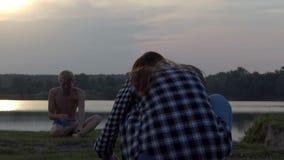 A mulher planeia disparar em um iogue em um banco do lago no slo-mo vídeos de arquivo
