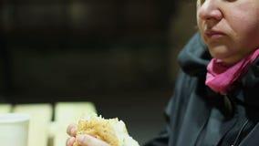 Mulher pobre esfomeado que come a grande parcela de comida lixo, hamburguer cortante avidamente video estoque