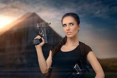Mulher poderosa que guarda o estilo do filme de ação da arma Fotografia de Stock Royalty Free