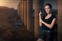 Mulher poderosa que guarda o estilo do filme de ação da arma Imagens de Stock