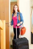 Mulher positiva bonito nas calças de brim com a bagagem que sae da casa Imagens de Stock Royalty Free
