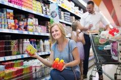 Mulher positiva com a família que guarda o iogurte Fotografia de Stock