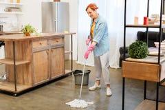 Mulher positiva concentrada no assoalho doméstico da lavagem do equipamento com espanador imagens de stock