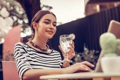 Mulher positiva deleitada que guarda um cocktail delicioso fotografia de stock