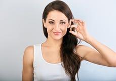 Mulher positiva natural de sorriso feliz que guarda a cápsula da vitamina E na mão no fundo azul closeup fotografia de stock royalty free