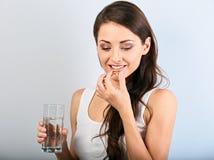 Mulher positiva natural de sorriso feliz que guarda a cápsula da vitamina E na mão e no vidro da água pura closeup fotografia de stock