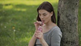 Mulher positiva nova que bebe o batido fresco atrav?s de uma palha que senta-se no parque do ver?o filme