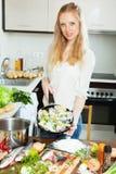 Mulher positiva que cozinha peixes Imagens de Stock