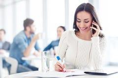 Mulher positiva que fala no telefone celular Fotografia de Stock