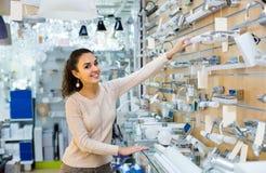 Mulher positiva que faz a compra na loja da iluminação foto de stock