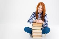 Mulher positiva que senta-se perto da pilha de livros e que usa o telefone celular Fotografia de Stock Royalty Free