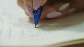 A mulher próxima da vista com tratamento de mãos elegante escreve no registro filme