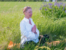 A mulher pratica a ioga fora foto de stock
