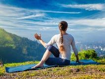 A mulher pratica o asana Marichyasana da ioga imagem de stock