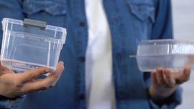 A mulher prefere o recipiente reusável do plástico do alimento ao descartável, economia video estoque