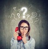 A mulher preocupada confusa que fala em um telefone tem muitas perguntas foto de stock royalty free