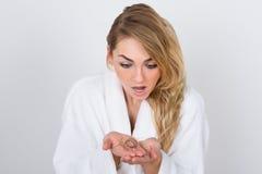 Mulher preocupada que guarda o cabelo da perda Fotografia de Stock