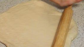 A mulher prepara a massa para a pizza Massa para a pizza e o rolamento-pino na tabela Desenrole a massa video estoque