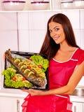 A mulher prepara peixes no forno Imagem de Stock
