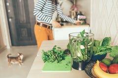 A mulher prepara produtos para um batido verde foto de stock royalty free